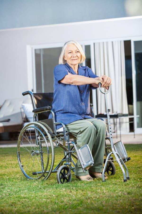 Mujer mayor que se sienta en la silla de ruedas en la clínica de reposo fotografía de archivo