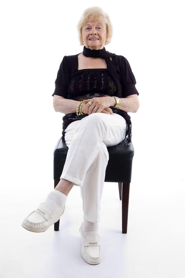 Mujer mayor que se sienta en silla fotografía de archivo