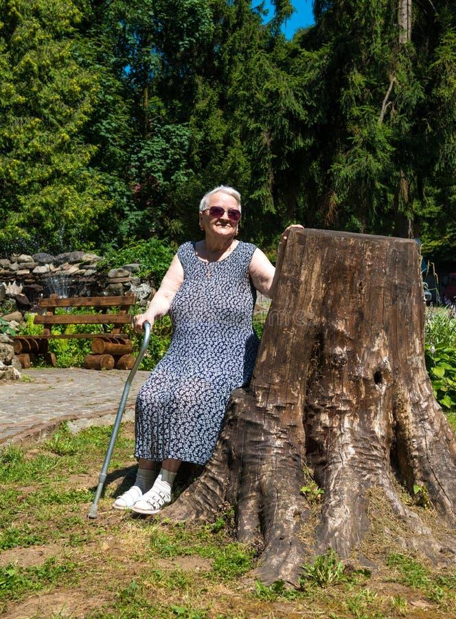Mujer mayor que se sienta en un banco fotos de archivo libres de regalías