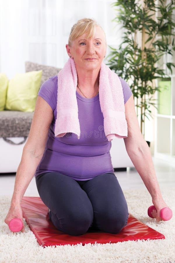 Mujer mayor que se sienta en una estera en casa y ejercicio con los pesos imagen de archivo