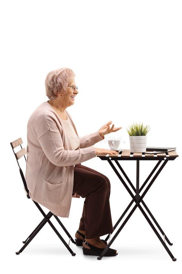 Mujer mayor que se sienta en una tabla con café y que gesticula con la mano imágenes de archivo libres de regalías