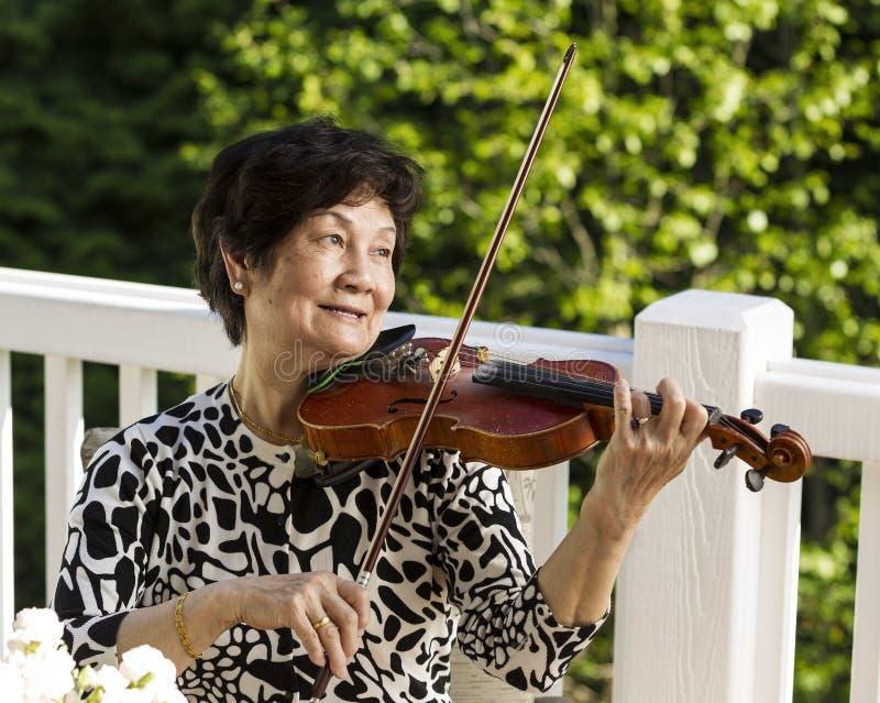 Mujer mayor que se sienta mientras que toca su violín al aire libre fotos de archivo libres de regalías