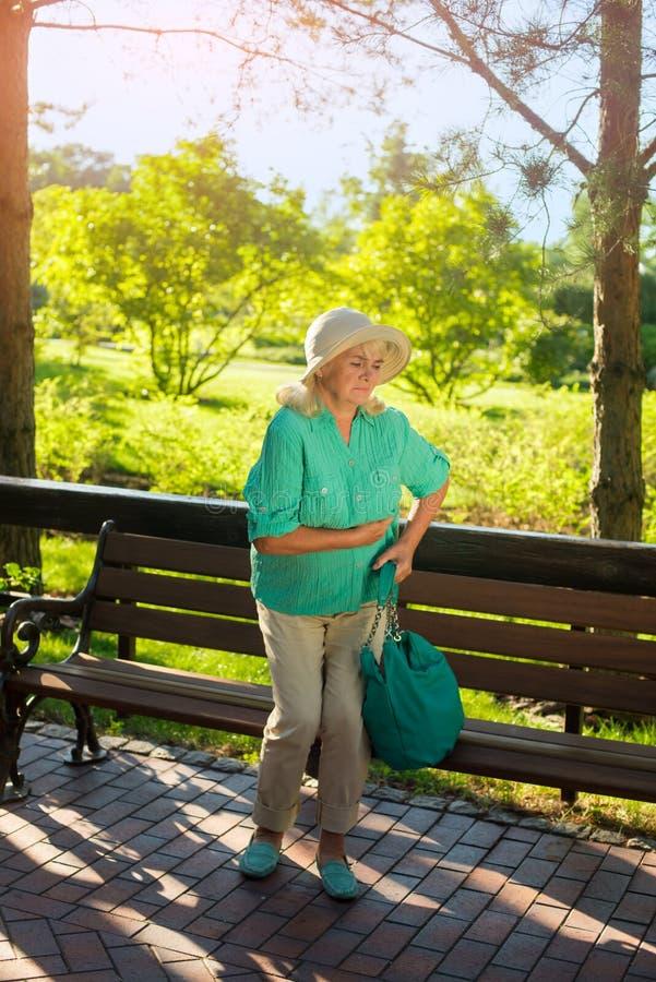Mujer mayor que se sostiene el estómago imagenes de archivo