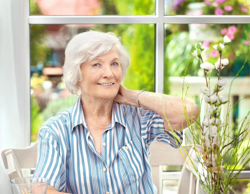 Mujer mayor que sienta en casa 5 fotografía de archivo