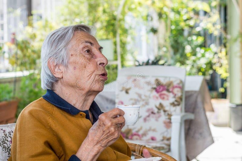 Mujer mayor que sienta y que bebe el café turco en el balcón en un día soleado fotos de archivo