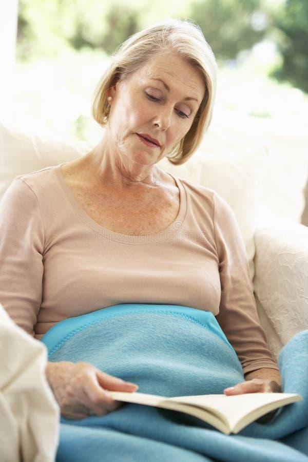 Mujer mayor que siente la reclinación mal debajo de la manta imagenes de archivo