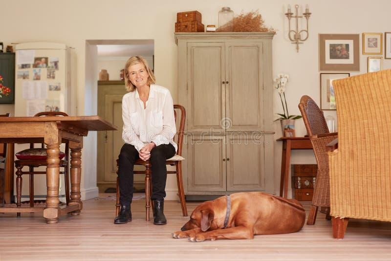 Mujer mayor que sonríe con confianza en su hogar con el perro imágenes de archivo libres de regalías