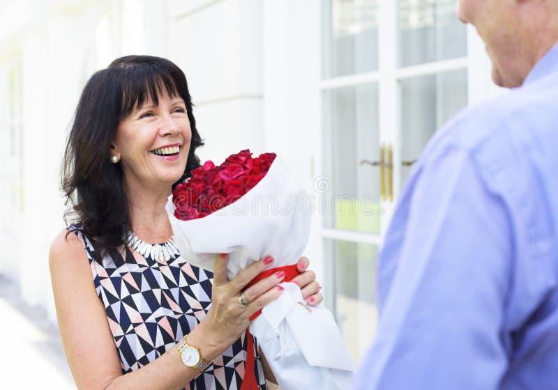Mujer mayor que sostiene el ramo de rosas fotos de archivo