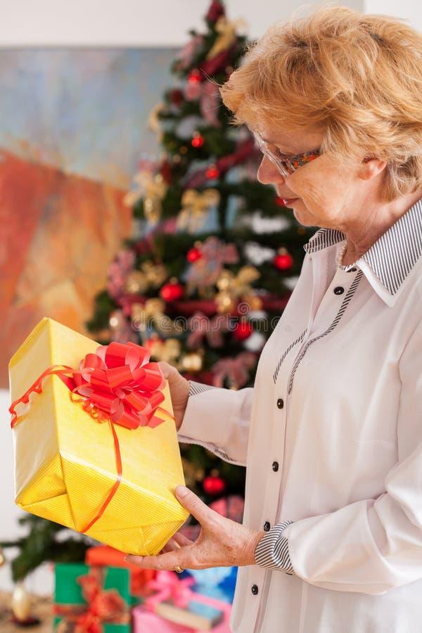 Mujer mayor que sostiene el regalo de la Navidad foto de archivo