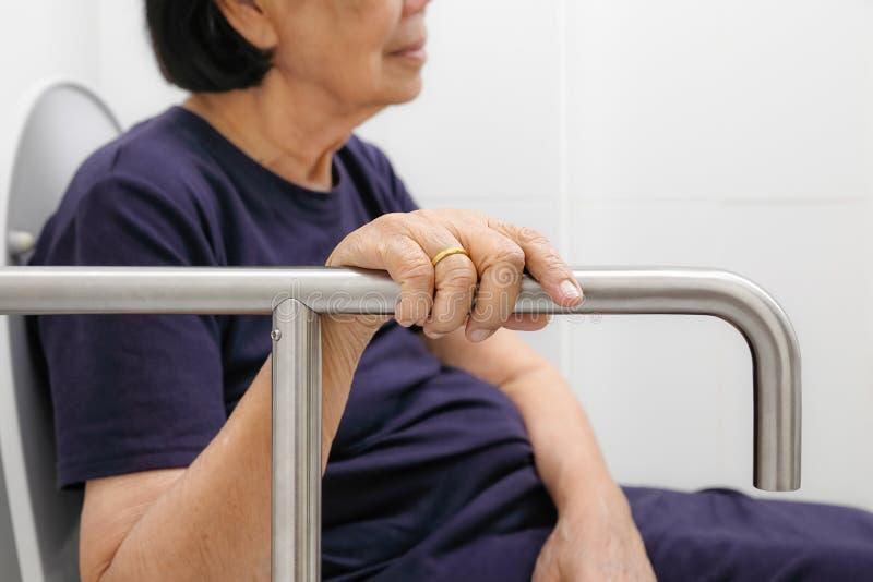 Mujer mayor que sostiene encendido la barandilla en retrete imagenes de archivo