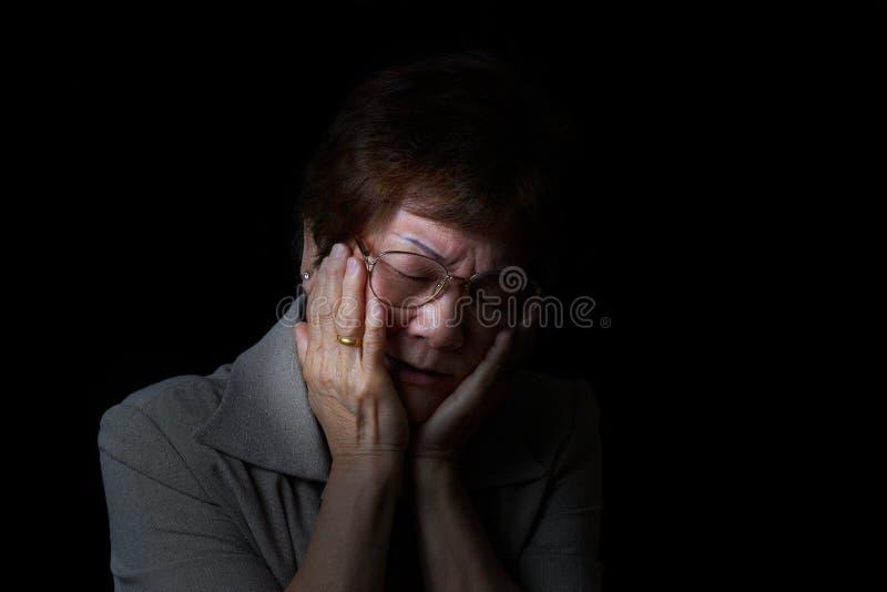 Mujer mayor que sostiene la cara mientras que en dolor en fondo negro fotos de archivo