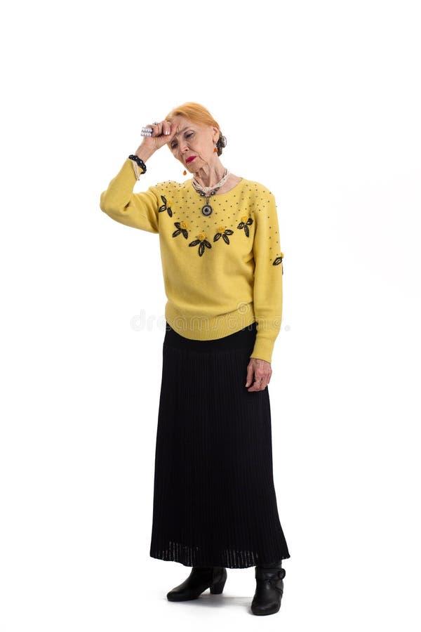 Mujer mayor que sostiene píldoras aisladas imagen de archivo libre de regalías