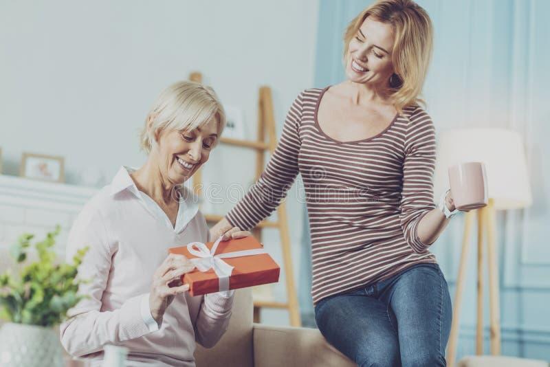 Mujer mayor que sostiene un regalo y que se sienta con su hija fotos de archivo libres de regalías