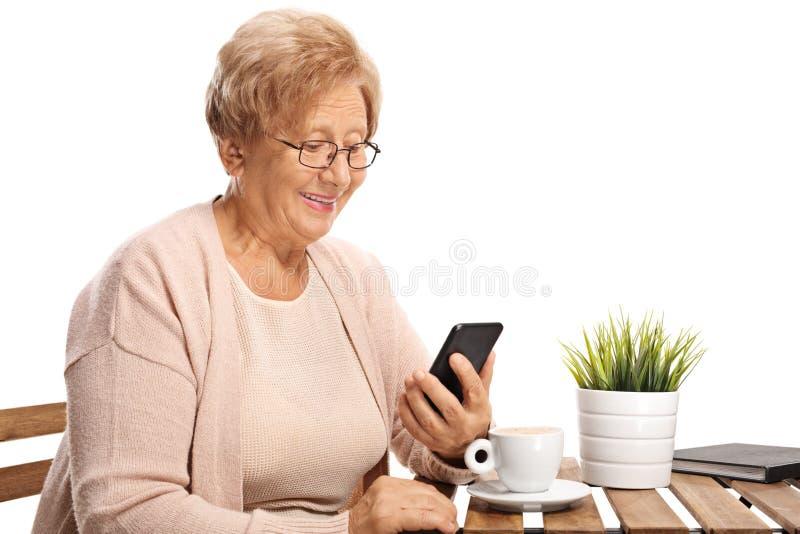 Mujer mayor que sostiene un teléfono móvil y que se sienta en una mesa de centro aislada en el fondo blanco fotos de archivo