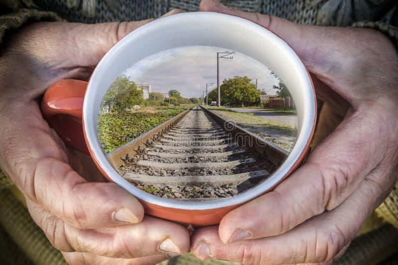 mujer mayor que sostiene una taza de té El círculo refleja los carriles del tren fotografía de archivo libre de regalías