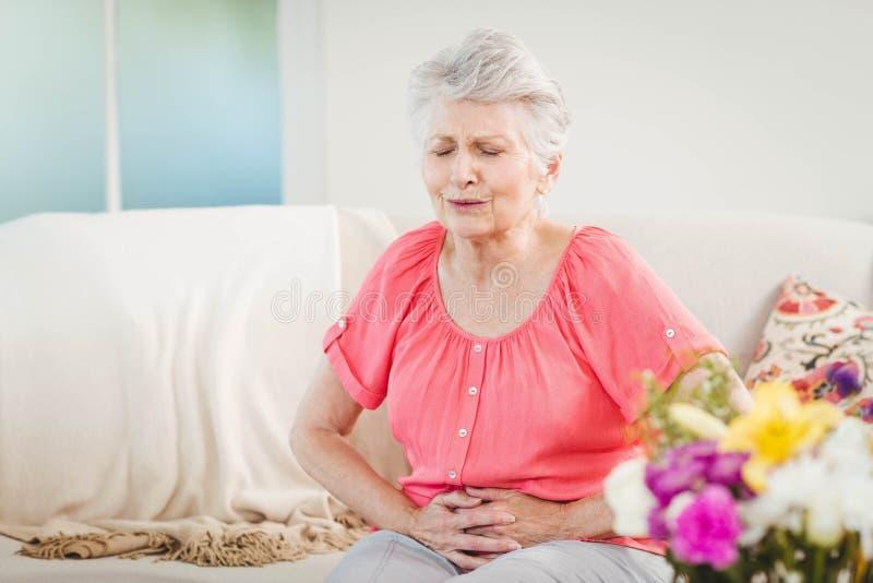 Mujer mayor que sufre de dolor de estómago imagenes de archivo