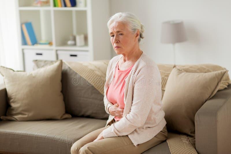 Mujer mayor que sufre de dolor de estómago en casa fotos de archivo