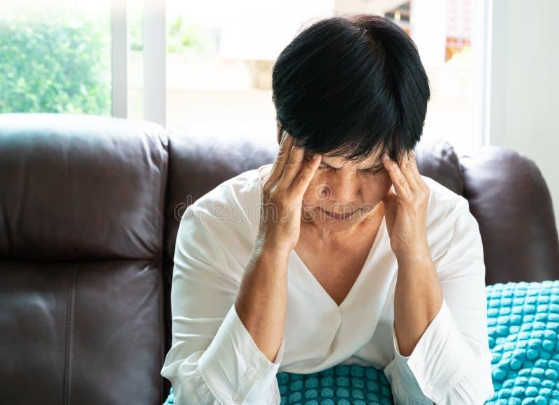 Mujer mayor que sufre del dolor de cabeza, tensión, jaqueca, concepto del problema de salud imagen de archivo