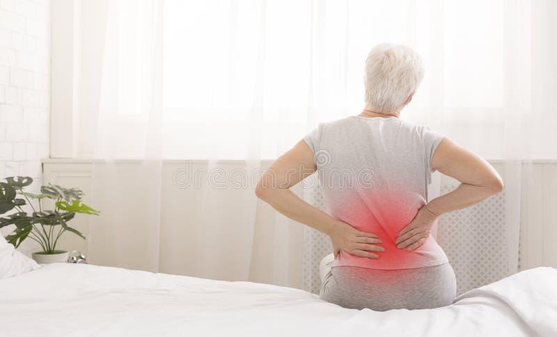 Mujer mayor que sufre del dolor de espalda que se sienta en cama imagenes de archivo