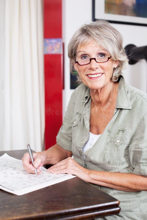 Mujer mayor que termina un crucigrama fotografía de archivo libre de regalías
