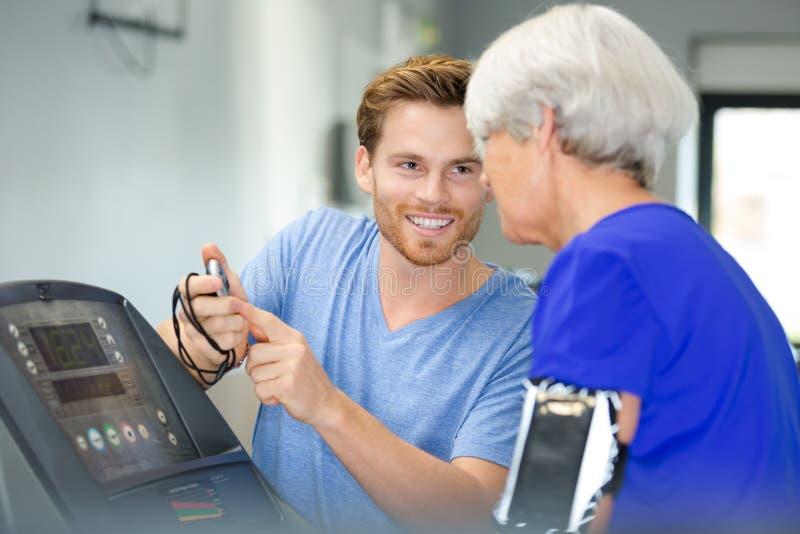 Mujer mayor que tiene charla amistosa con el instructor personal imágenes de archivo libres de regalías
