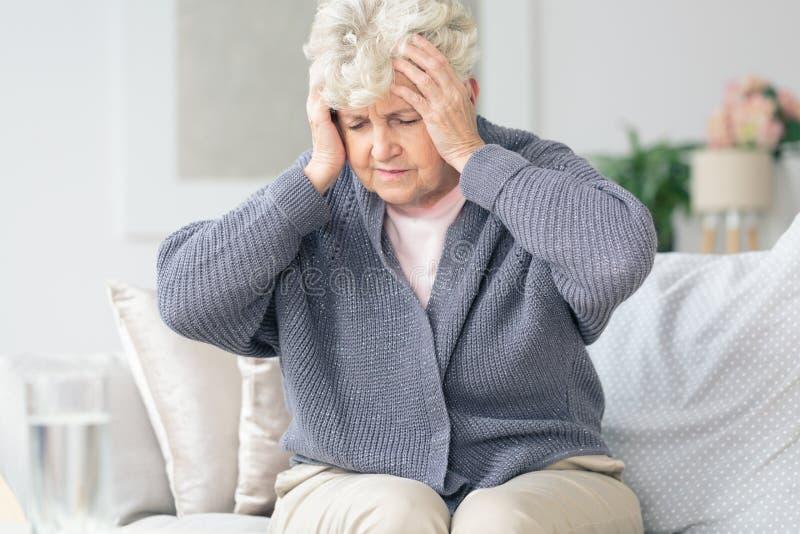Mujer mayor que tiene dolor de cabeza de la jaqueca foto de archivo
