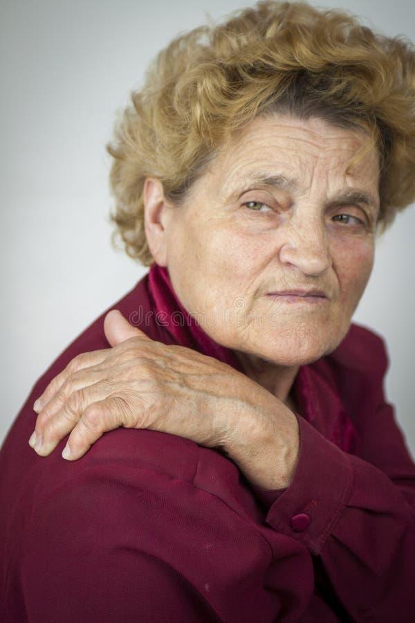 Mujer mayor que tiene dolor trasero imagen de archivo