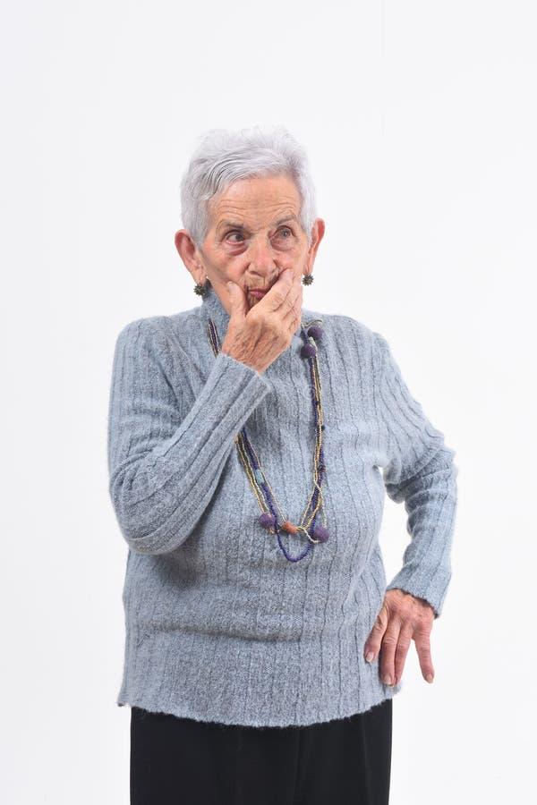 Mujer mayor que tiene dudas y preguntas sobre el fondo blanco imagen de archivo