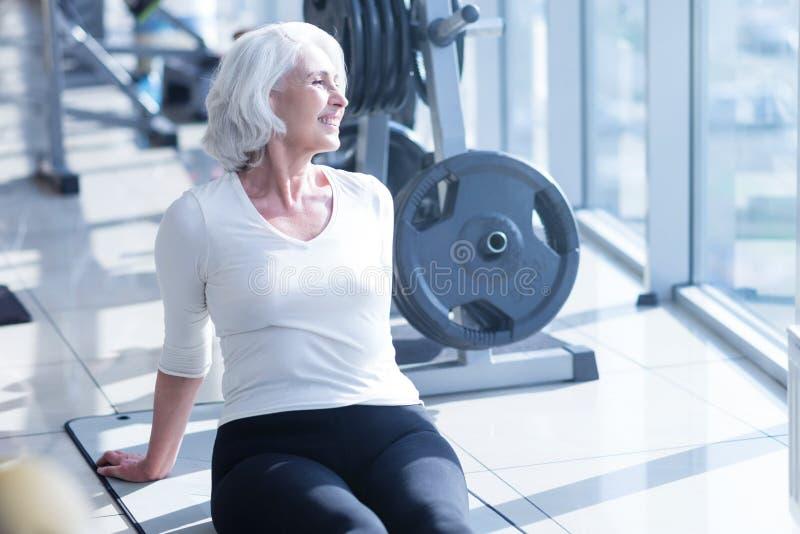 Mujer mayor que tiene resto en el gimnasio imagen de archivo