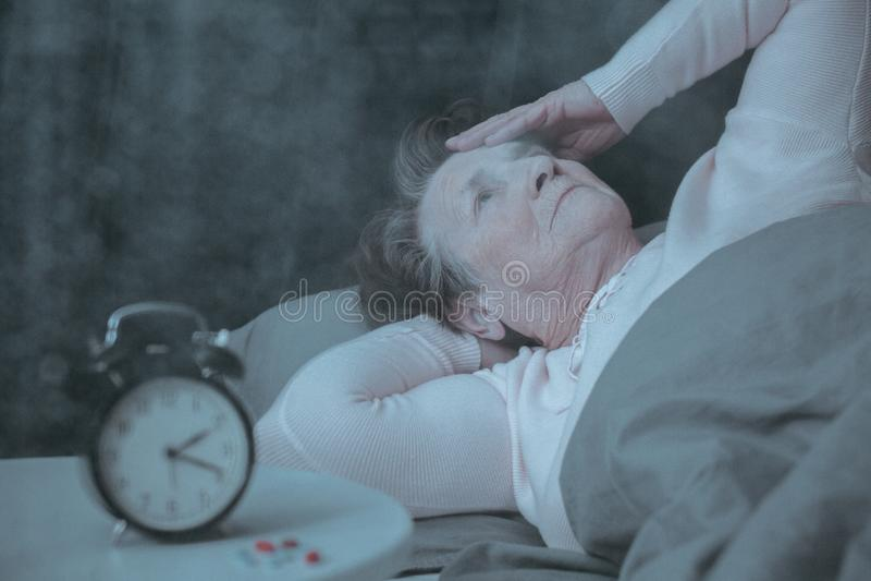 Mujer mayor que tiene trastorno del sueño foto de archivo