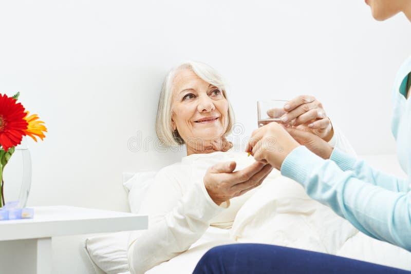Mujer mayor que toma píldoras con agua fotos de archivo