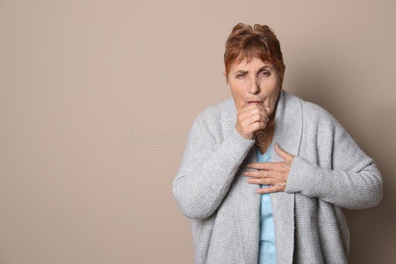 Mujer mayor que tose contra fondo del color imágenes de archivo libres de regalías