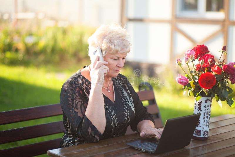 Mujer mayor que trabaja con el cuaderno, mecanografiando, hablando en el teléfono foto de archivo libre de regalías