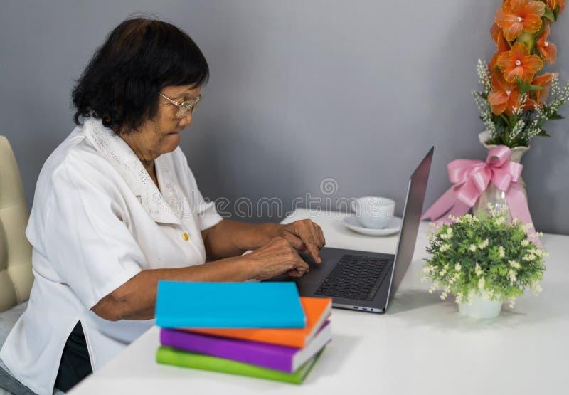 Mujer mayor que trabaja en el ordenador portátil imagen de archivo libre de regalías