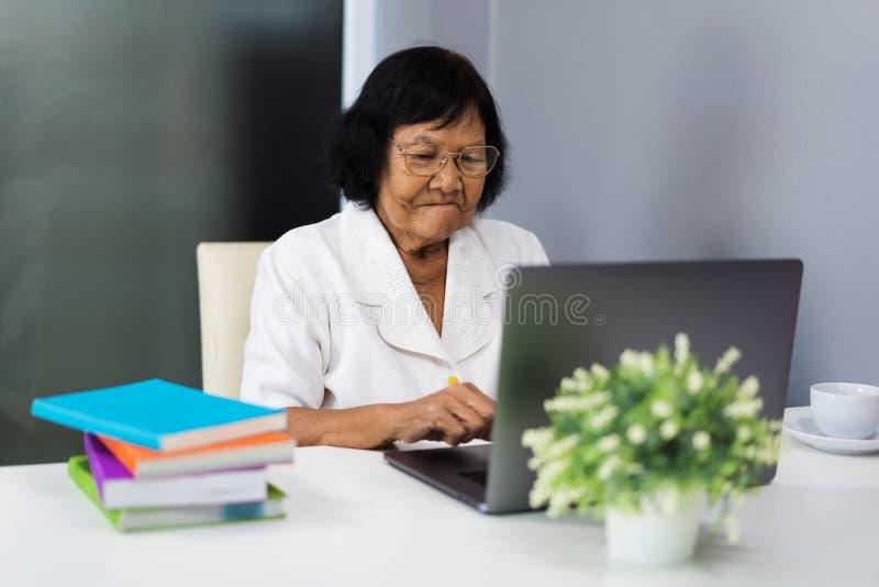 Mujer mayor que trabaja en el ordenador portátil fotografía de archivo