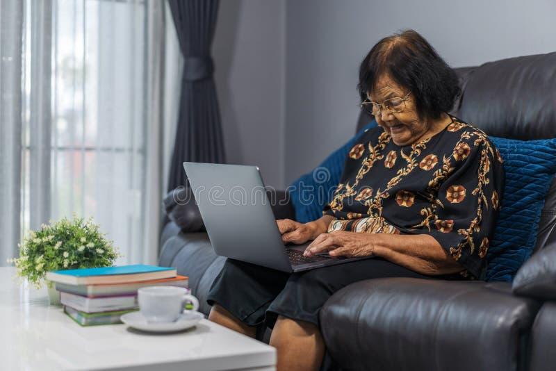 Mujer mayor que trabaja en el ordenador portátil en sala de estar imágenes de archivo libres de regalías