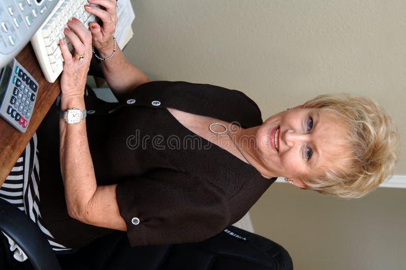 Mujer mayor que trabaja en oficina fotografía de archivo
