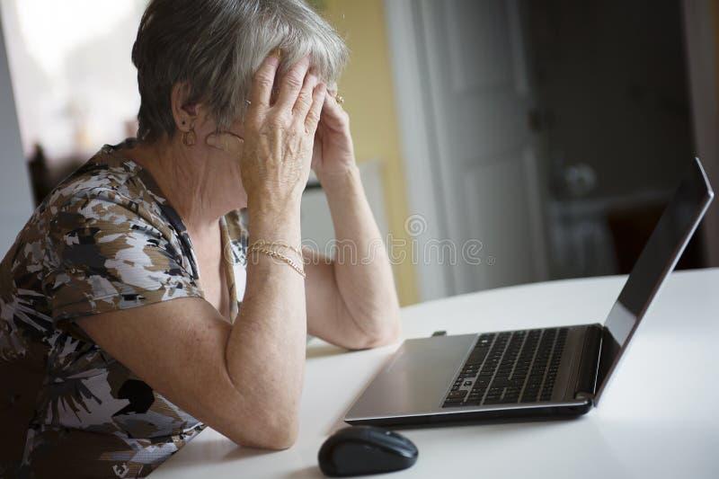 Mujer mayor que trabaja en su ordenador portátil en su cocina foto de archivo libre de regalías
