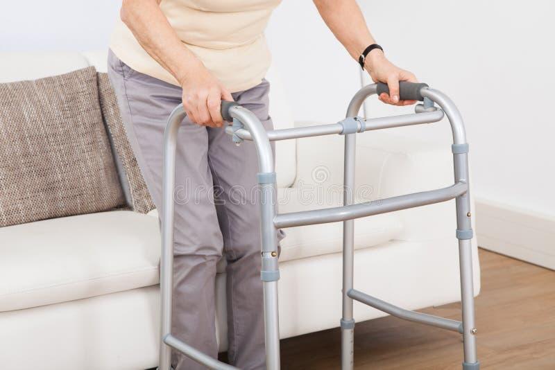 Mujer mayor que usa el marco que camina imagen de archivo