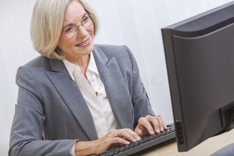 Mujer mayor que usa el ordenador imagenes de archivo