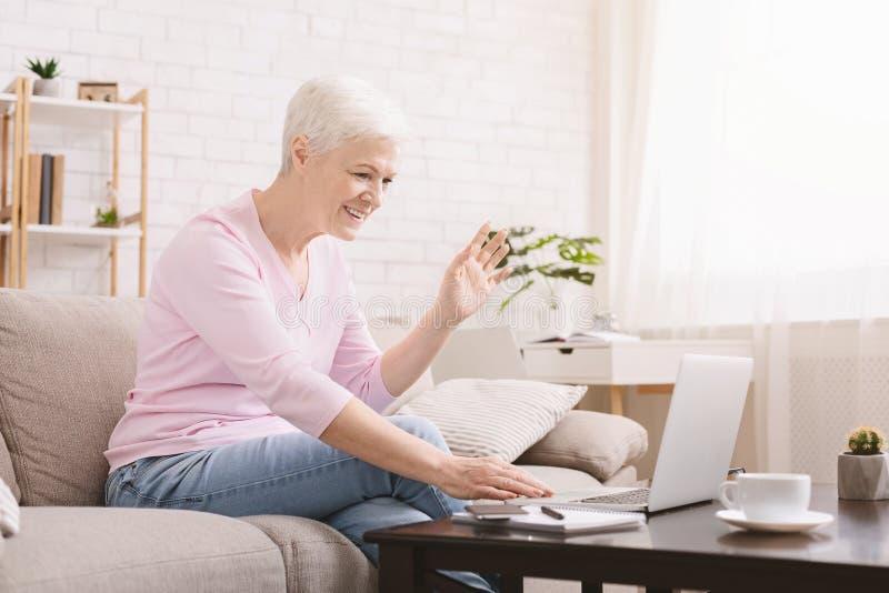 Mujer mayor que usa el ordenador portátil para la llamada video con su familia imagen de archivo libre de regalías