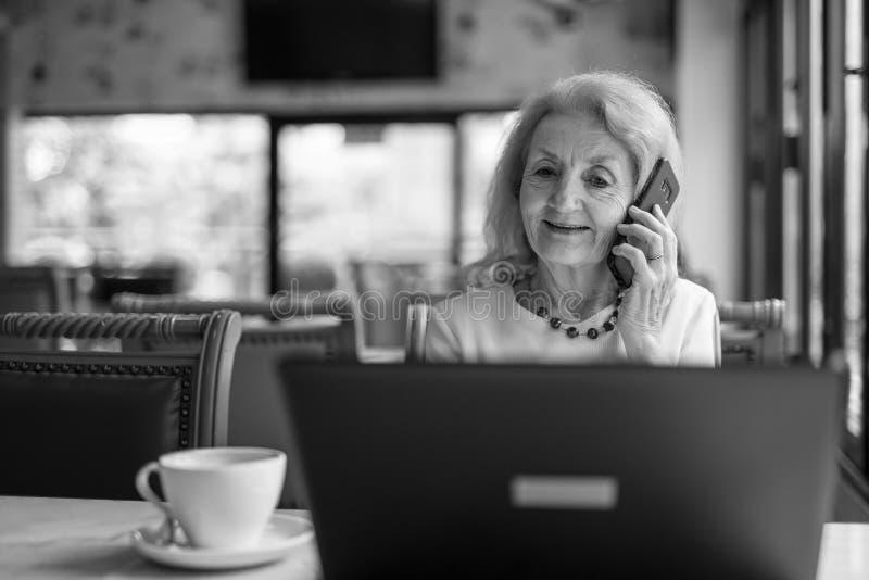 Mujer mayor que usa el ordenador portátil y el teléfono móvil fotos de archivo libres de regalías