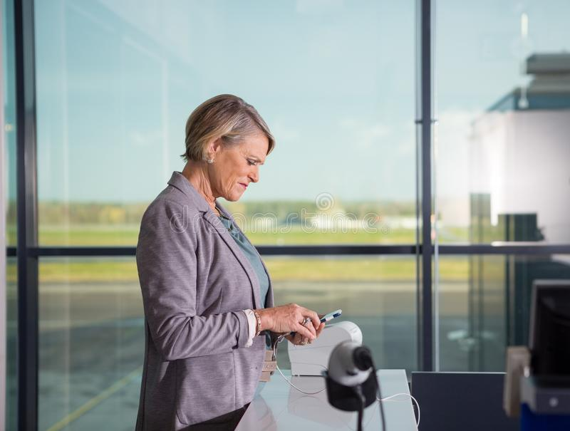 Mujer mayor que usa el teléfono móvil en aeropuerto imagen de archivo