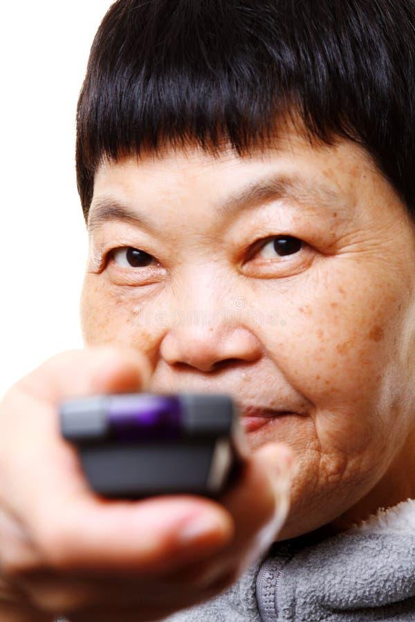 Mujer mayor que usa el telecontrol de la TV fotos de archivo libres de regalías