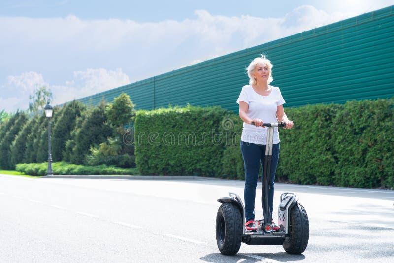 Mujer mayor que usa el transportador personal eléctrico foto de archivo libre de regalías