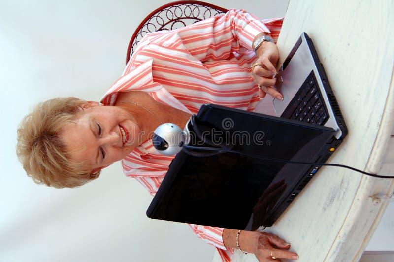 Mujer mayor que usa el webcam fotografía de archivo libre de regalías