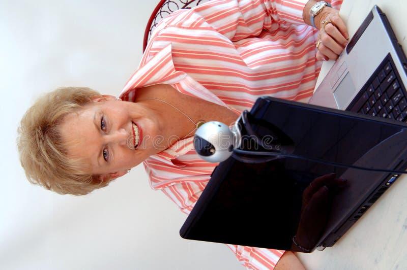 Mujer mayor que usa el webcam fotos de archivo