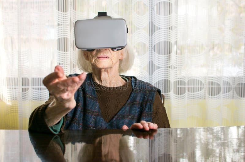 Mujer mayor que usa gafas de la realidad virtual fotos de archivo