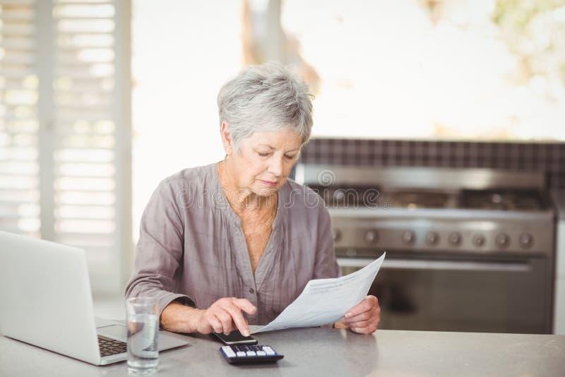 Mujer mayor que usa la calculadora mientras que lleva a cabo el documento foto de archivo libre de regalías