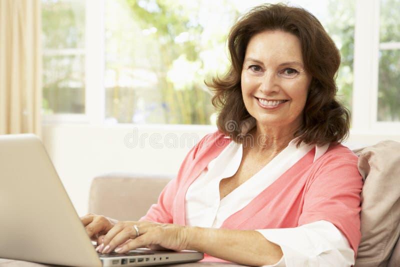 Mujer mayor que usa la computadora portátil en el país foto de archivo libre de regalías